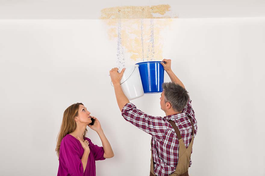 man catching dripping water from ceiling